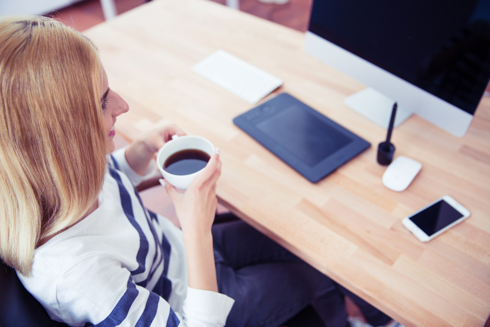 Top view portrait of a girl drinking coffee in office