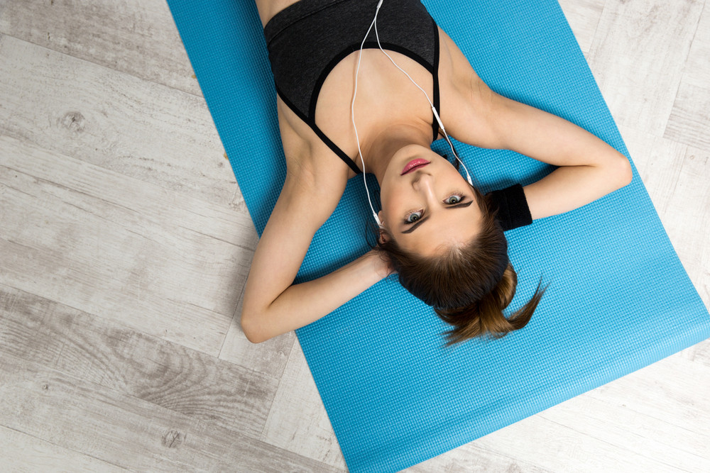 Top view portrait of a young woman resting on the yoga mat at gym