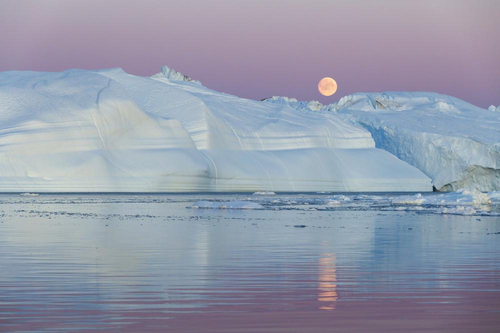 Towering iceberg against a full moon
