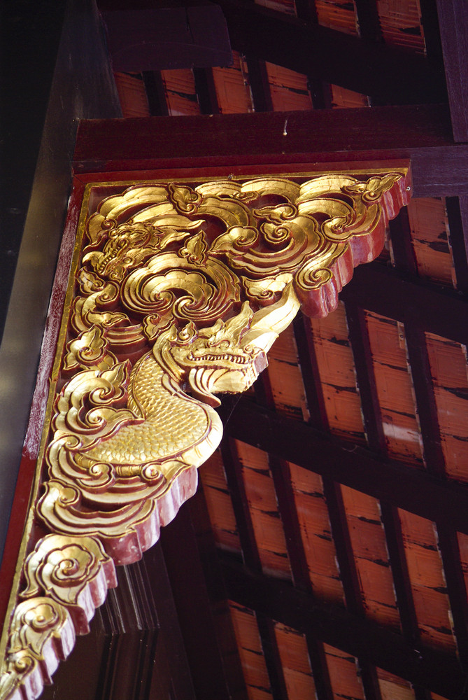 Traditional Thai fine art on a window and roof Temple Chiangmai Thailand