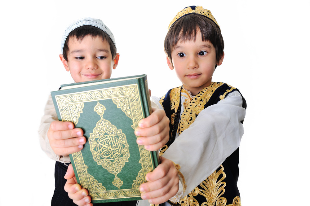 Two beautiful kids holding holy Qoran