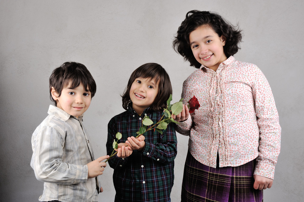 Two brothers and sister with beautiful red rose