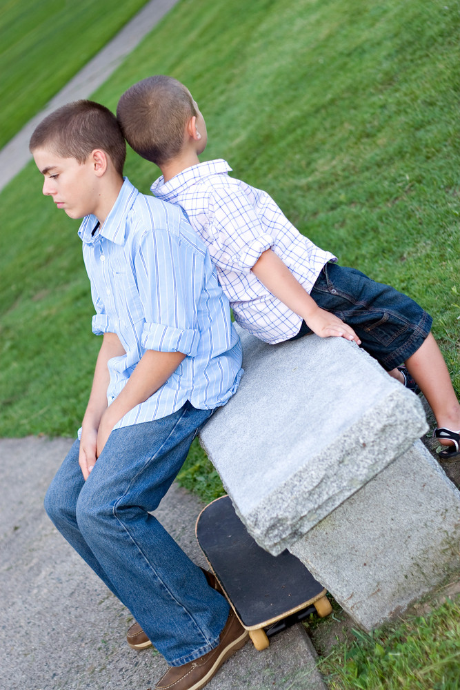 Two brothers sitting back to back on a bench in the park looking very bored.