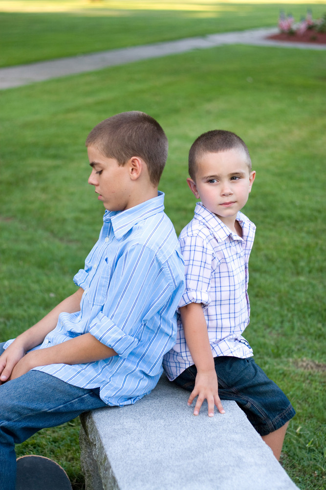 Two brothers sitting back to back on a bench in the park.