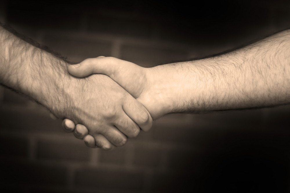 Two business men shaking hand in sepia tone over a brick wall backdrop.