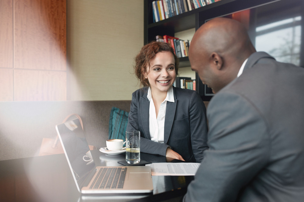 Two business partners sitting in cafe and discussing business plan. Businessman and businesswoman smiling during meeting in a coffee shop.