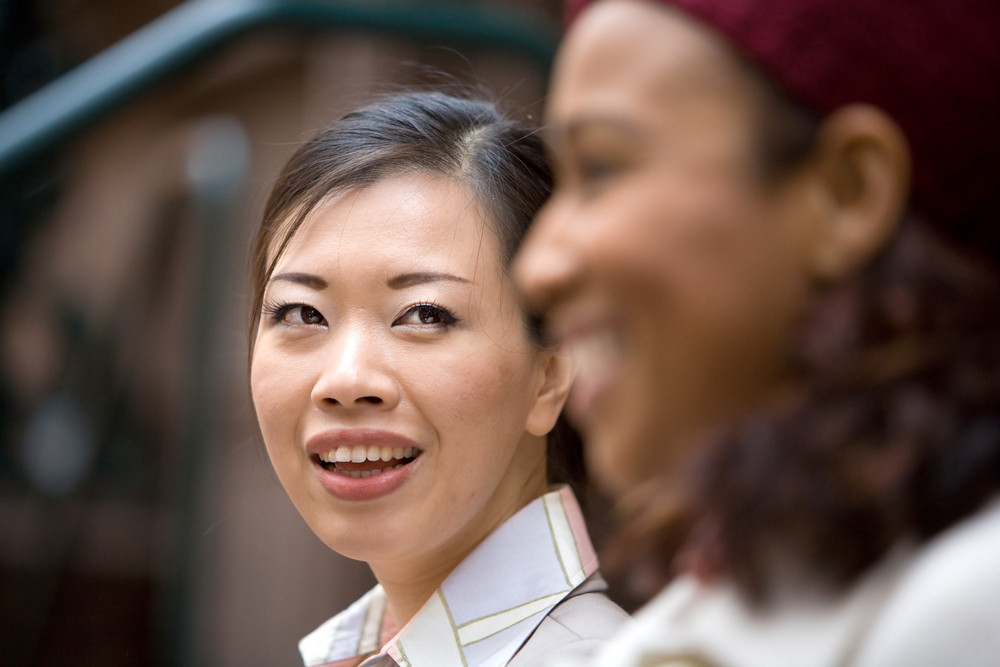 Two business women having a casual meeting or discussion in the city. Shallow depth of field.