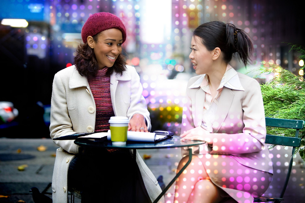 Two business women having a casual meeting or discussion in the city with an abstract glowing halftone circles effect.