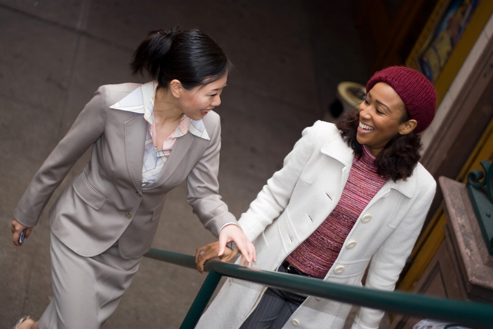 Two business women having a casual meeting or discussion while walking in the city.