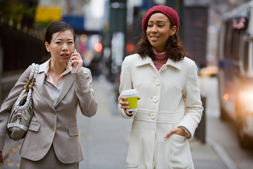 Two business women walking in the big city. One is on her cell phone.