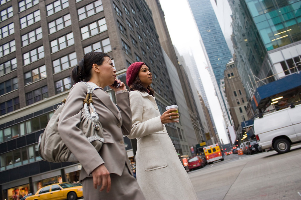 Two business women walking in the big city. One woman is on her cell phone.  Slightly shallow depth of field.