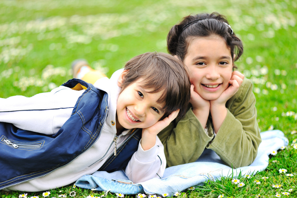 Two children laying on grass, brother and sister