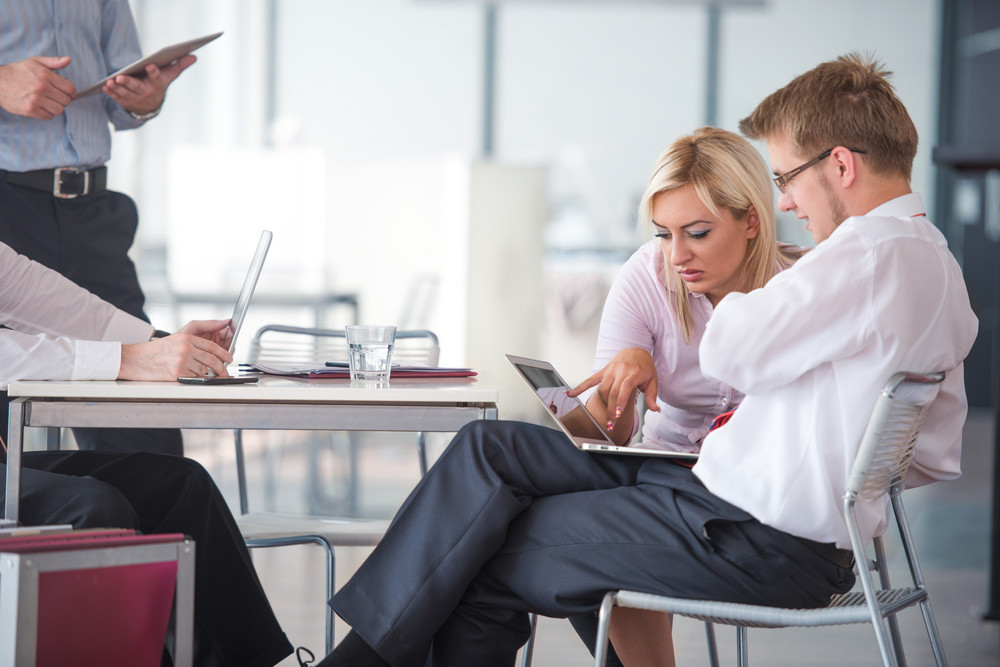 Two corporate people working with tablet in an office
