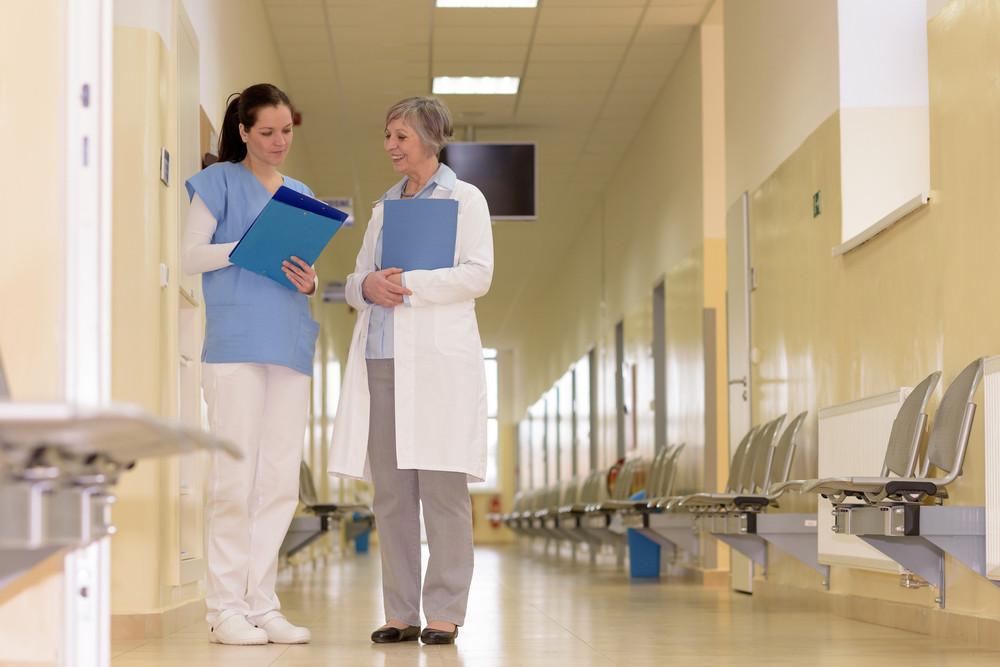 Two female doctors standing in empty hospital corridor