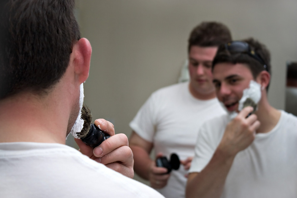 Two groomsmen shaving and gettin ready for the big event.  Shallow depth of field with focus on the foreground.