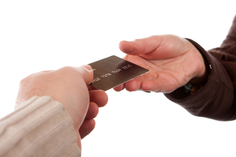 Two hands exchanging a credit debit or gift card isolated over a white background.