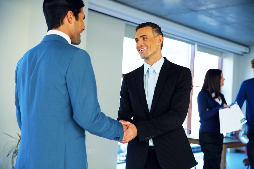 Two happy businessman handshaking in conference hall