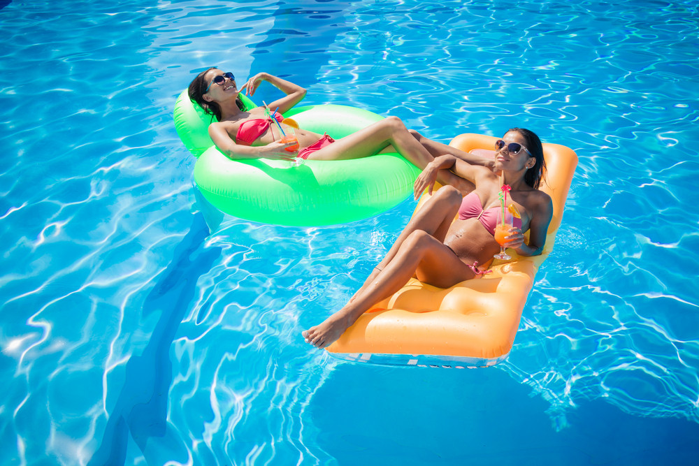 Two happy girls resting on air mattress in swimming pool with cocktails