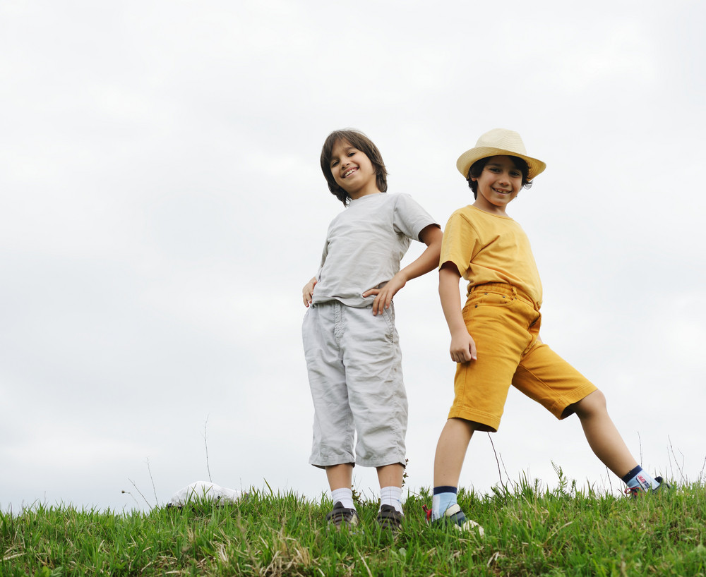 Two kids standing on a green meadow