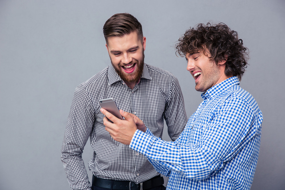 Two laughing men using smartphone