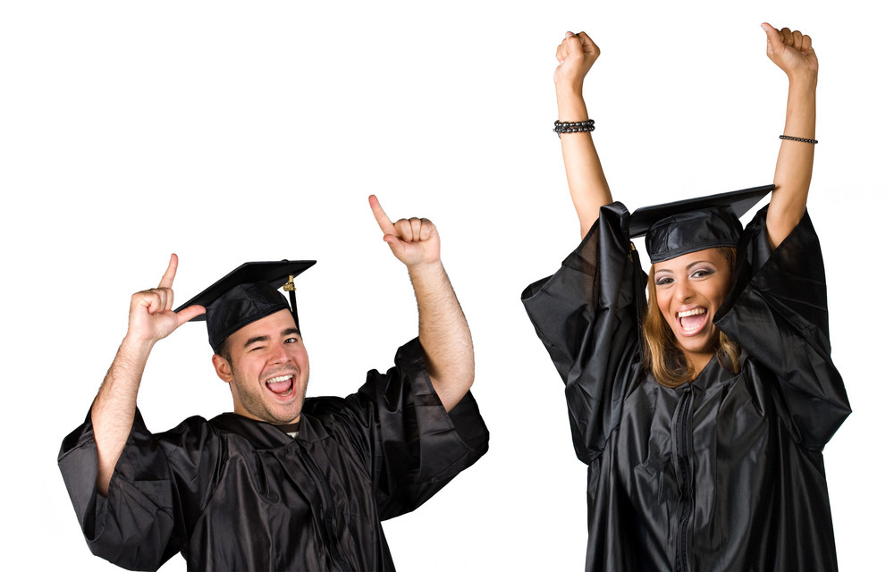 Two recent graduates posing in their caps and gowns isolated over white.