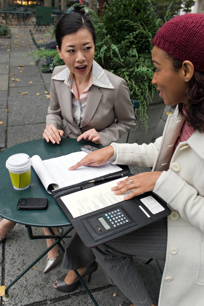 Two young business women discussing a group or team project in the park.