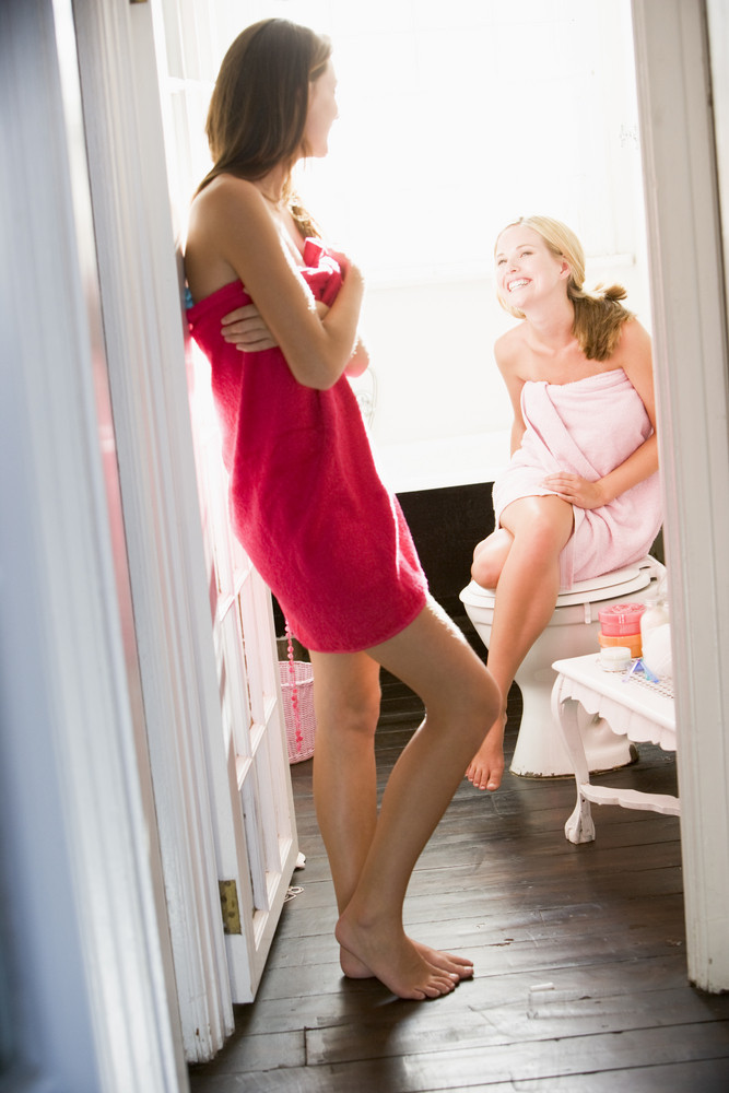 Two young women wearing towels and chatting in the bathroom