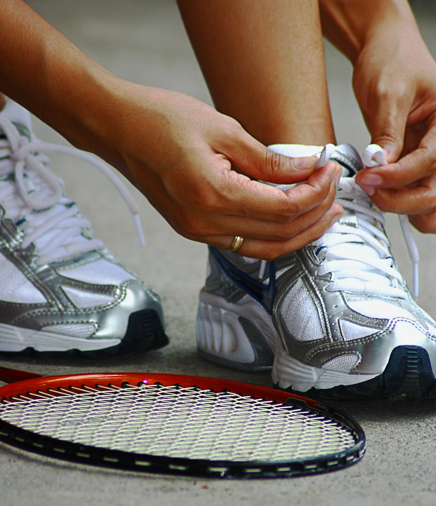 Tying Shoe Laces Ready For A Game Of Badminton