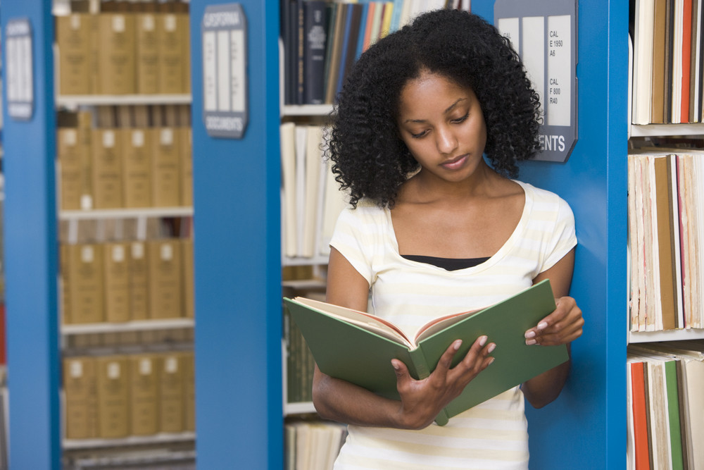 University student reading book in library