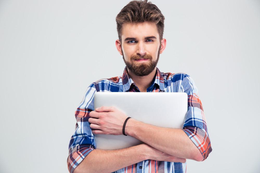 Unshaved handsome man holding laptop