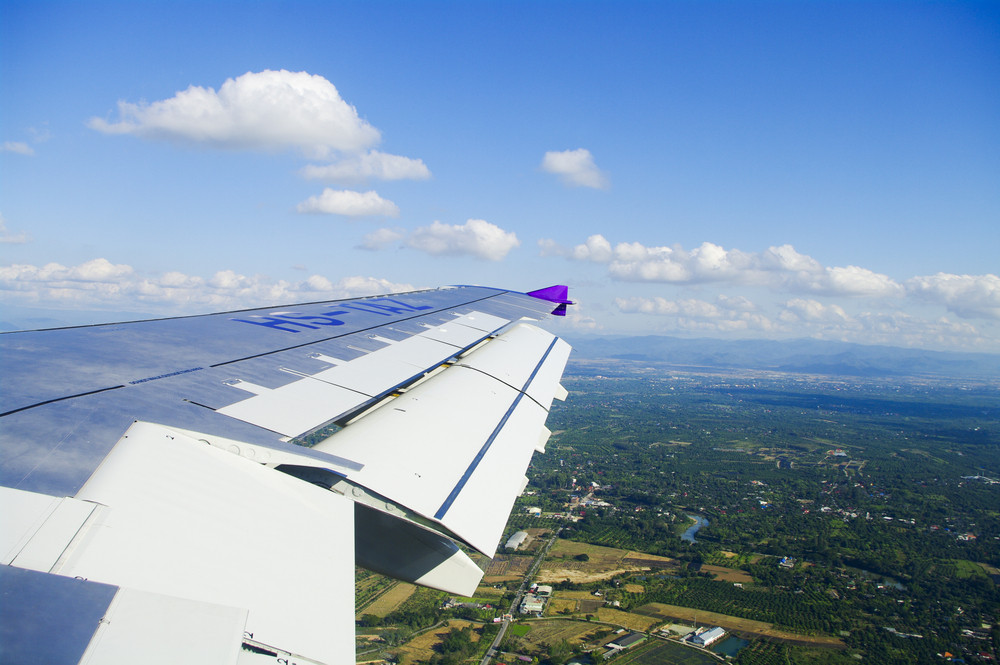 View of jet plane wing with city view