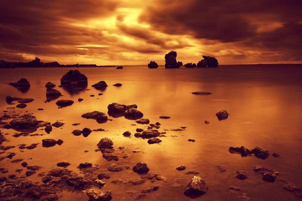 Dramatic sunset over rocky sea coast