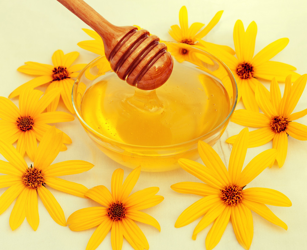 Honey and wooden spoon decorated with flowers