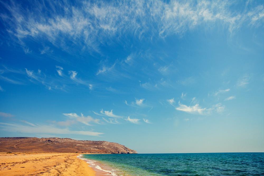 Wild deserted beach with cloudy sky