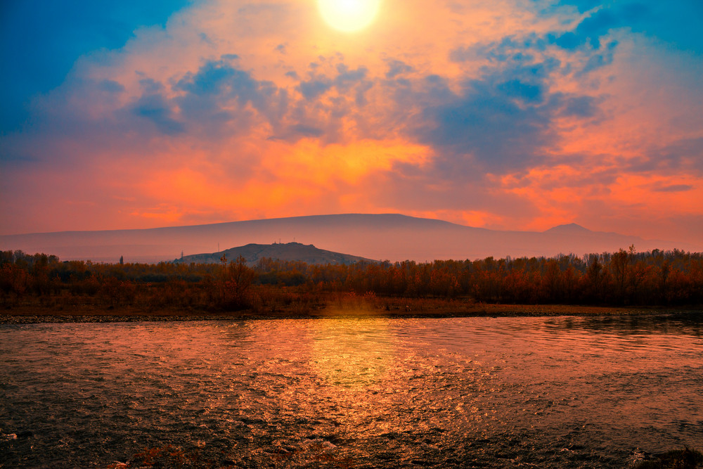 Foggy sunset over mountain river