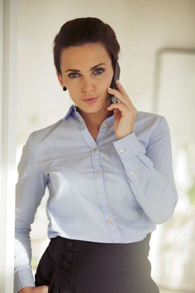Well dressed businesswoman talking on the phone looking at camera. Caucasian woman in the 20s with mobile phone.