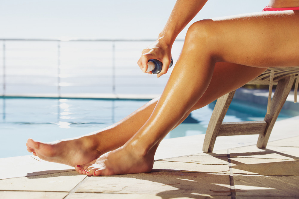 Woman applying suntan spray onto her legs. Female sitting on recliner chair by the swimming pool sunbathing.