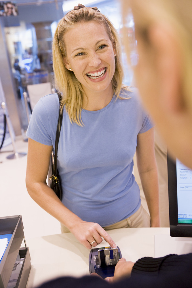 Woman entering security details for credit card purchase in store