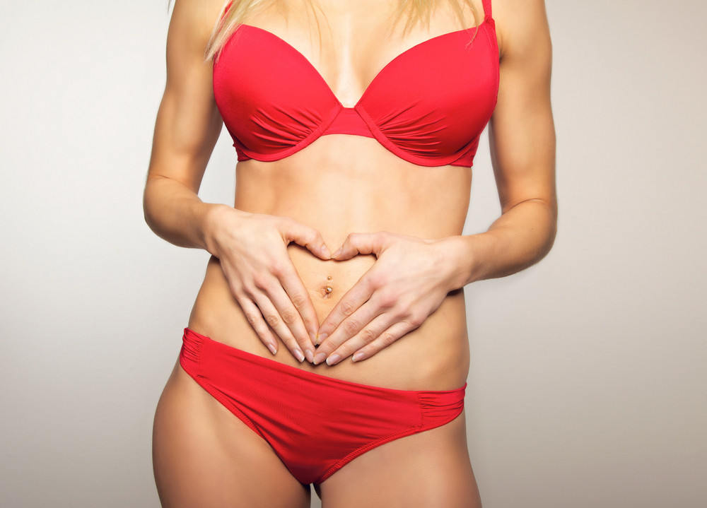 Woman holding hands on her flat stomach making a heart symbol