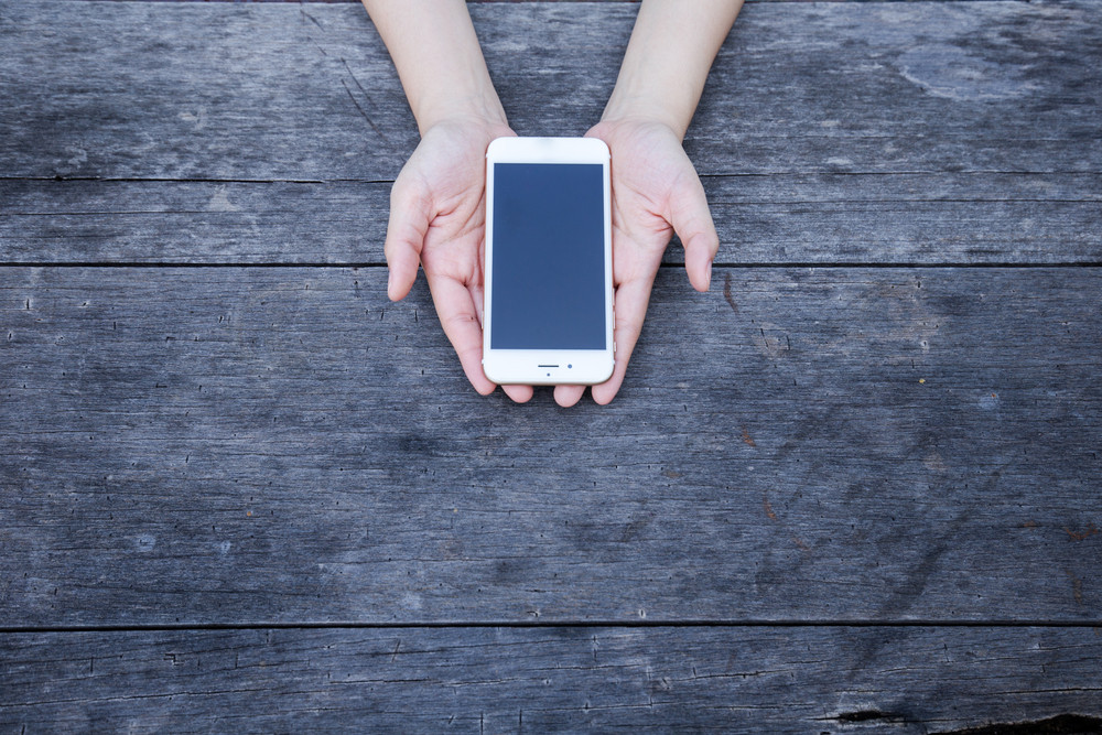 Woman holding smartphone on wood table.