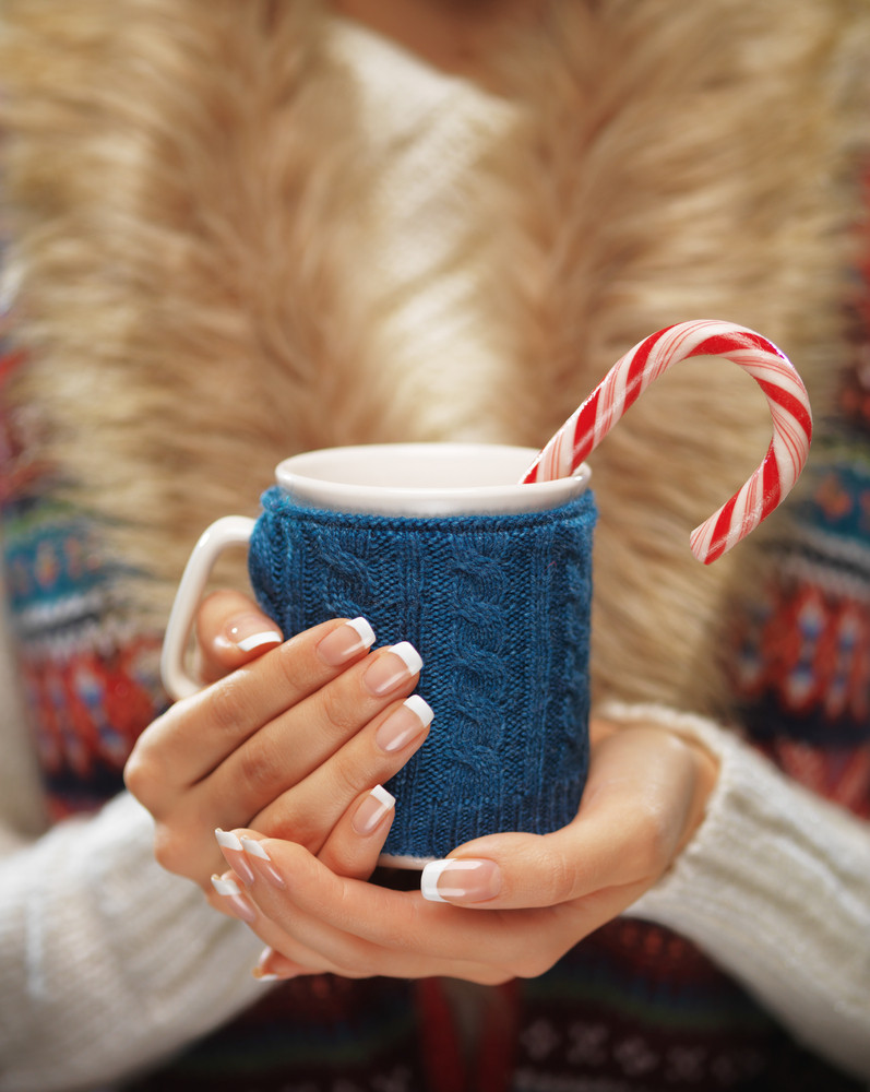 Woman holds a winter cup close up. Woman hands with elegant french manicure nails design holding a cozy knitted mug with hot cocoa or coffee with a mint candy cane. Winter and Christmas time concept.