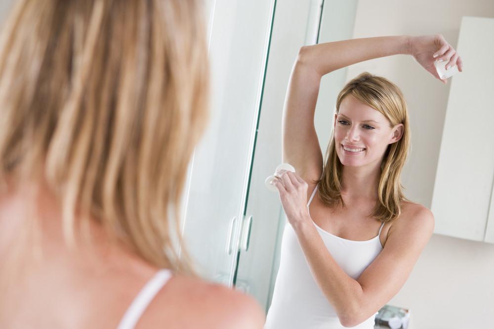 Woman in bathroom applying deodorant smiling