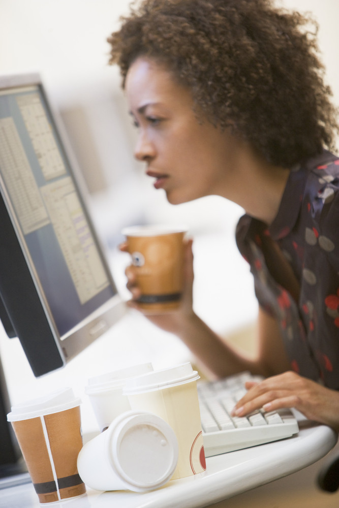 Woman in computer room with many cups of empty coffee around her