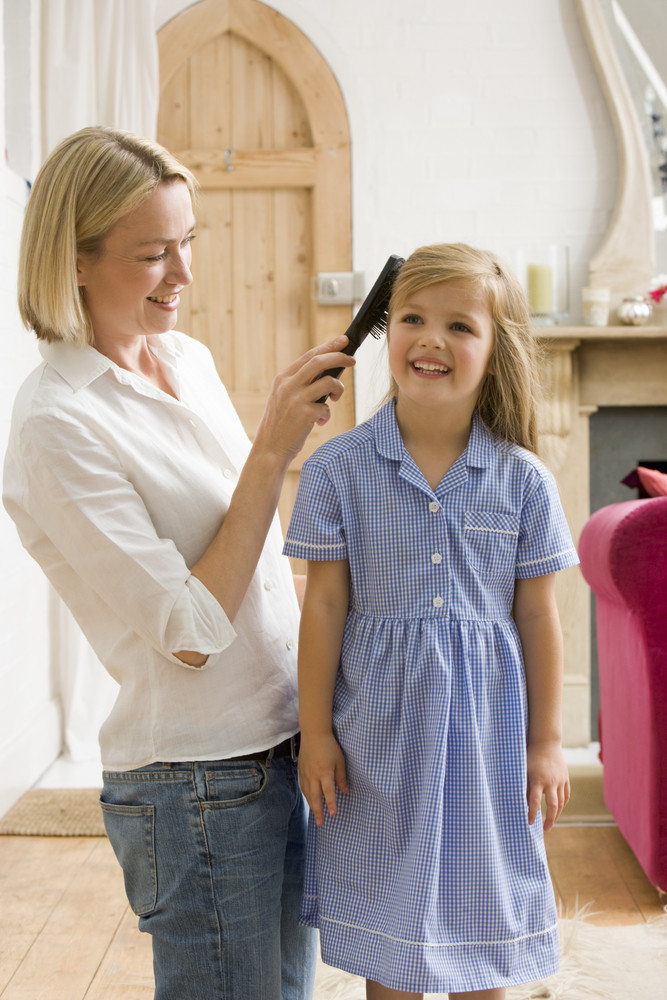 Woman in front hallway brushing young girl's hair and smiling