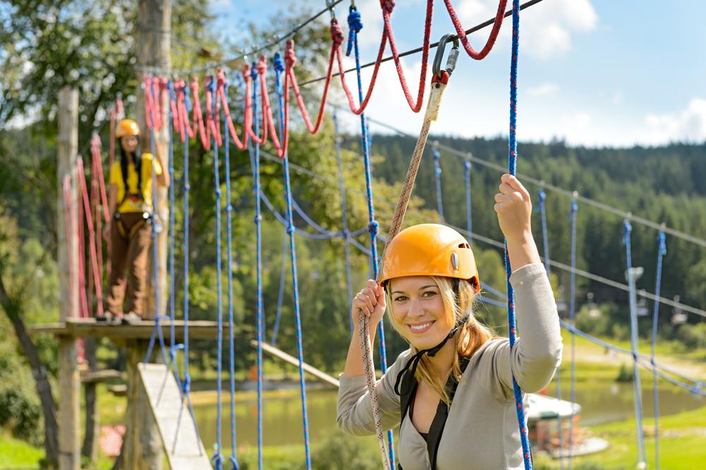 Woman in helmet climbing on rope ladder in adrenalin park