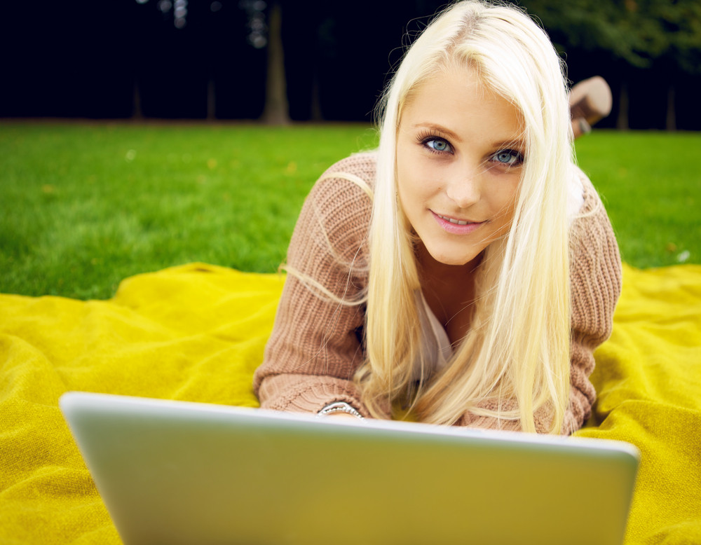 Woman in park with laptop relaxing