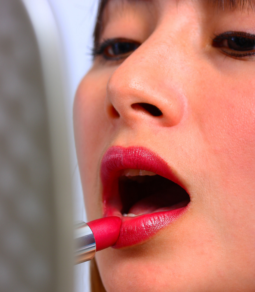 Woman Looking In The Mirror And Applying Lipstick