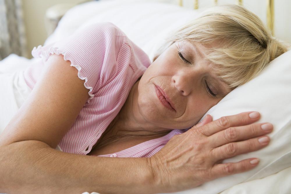 女性はベッドの睡眠に横たわって