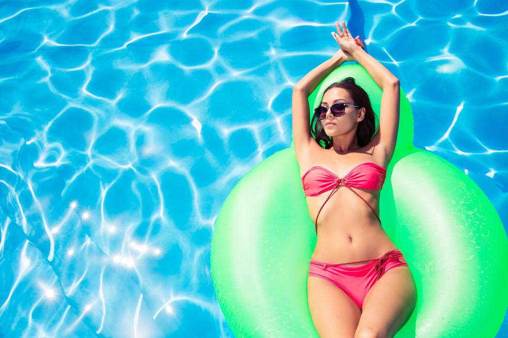 Woman lying on air mattress in swimming pool