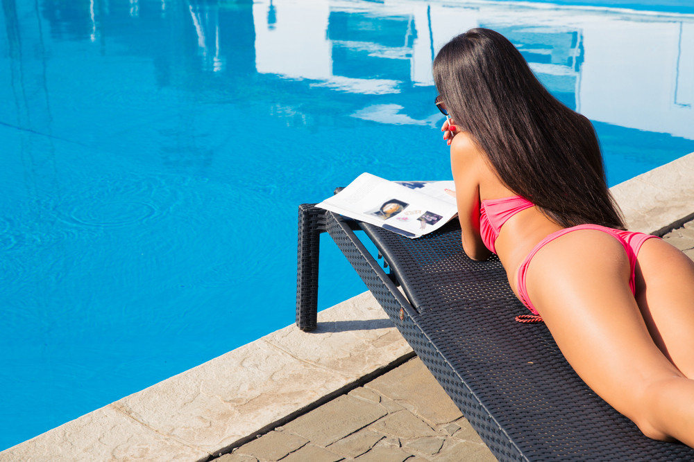 Woman lying on deckchair and reading magazine